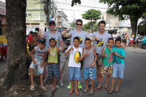 Dylan Grimes (Centre) with teammates and young Brazilian children in Rio
